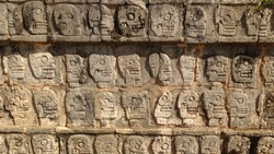 Skull sculptures on a wall at the Chichén Itzá archeological site, Yucatan, Mexico.