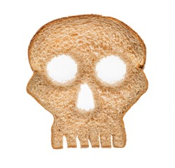 Skull shaped piece of bread cut from whole wheat loaf to illustrate danger from gluten in wheat products