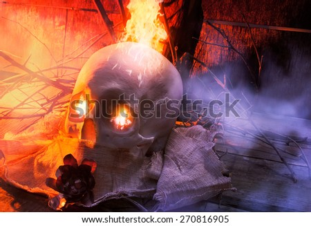 Stock Photo Skull with cloth and fire angle view. Anatomic white skull lying on wooden old surface with tree branches, fog, cloth & fantasy fire effect eyes composition.