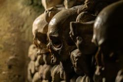 Skulls and bones in catacombs. Old broken skull placed in the wall of bones. Grim lighting. Underground cemetery.