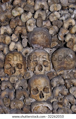 Skulls and bones piled in the Paris catacombs - stock photo