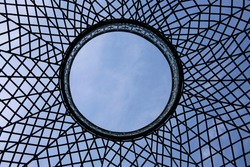 Sky above dome roof. Transparent circular ceiling or roof with grid structure. Close-up fragment of modern architecture with round pattern. Abstract geometric background with radial lines and sectors.