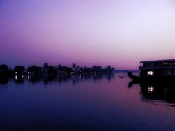 sky and a house boat in the evening reflecting in backwaters of Kerala India toned with a with a retro vintage instagram filter app or action effect