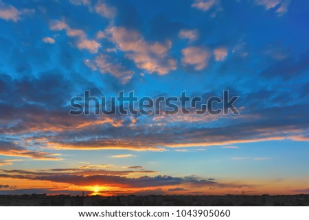 Sky and clouds at sunset over silhouettes buildings of the evening city.