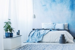 Sky blue bedroom interior with double bed, plants and grey boxes on the floor