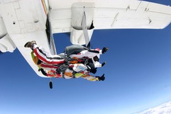 Sky diving tandem jumping from the plane in the blue skies