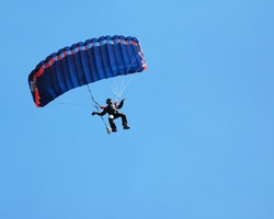 Sky Diving with space in solid blue sky for your text.