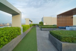 Sky garden on private rooftop of condominium or hotel, high rise architecture building with tree, grass field, and blue sky.