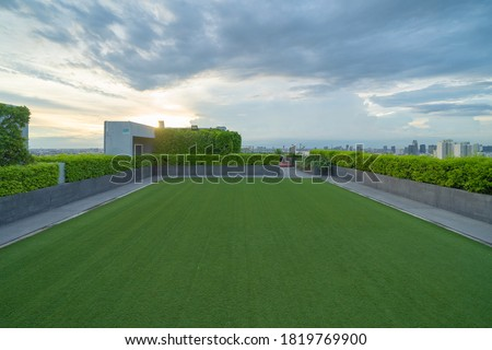 Sky garden on private rooftop of condominium or hotel, high rise architecture building with tree, grass field, and blue sky. Stock photo ©