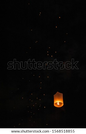 Sky lanterns, flying lanterns, floating lanterns, hot-air balloons on dark night sky with moon. New year and Yeepeng festival in Thailand. Chiang Mai, Northern Thailand.