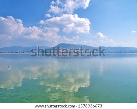 Sky mirroring  on  water at lake orestiada in Kastoria, Greece. Beautiful tranquil waterscape.