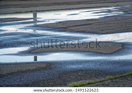 Sky reflected in a puddle of water on pavement, Early morning sunrise #1491522623