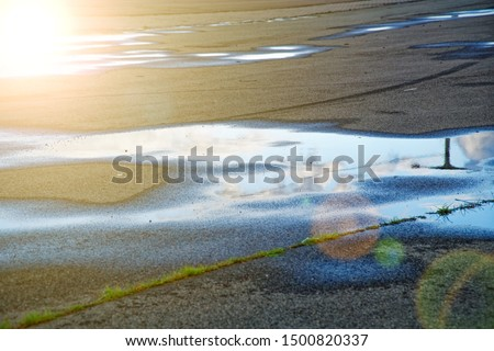 Sky reflected in a puddle of water on pavement, Early morning sunrise #1500820337