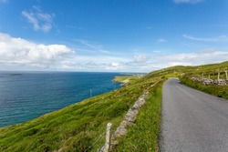 Sky Road with the most spectacular panoramic views of the Atlantic Ocean and Connemara coastline, paved path between green grass and rocks, sunny spring day in Clifden, County Galway, Ireland