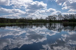 Sky with clouds and lake with reflection of sky and clouds divided by trees on the horizont. calm Nature scenary