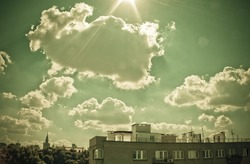 Sky with clouds and sun over the Warsaw. View from The University of Warsaw Library's roof. Retro style.