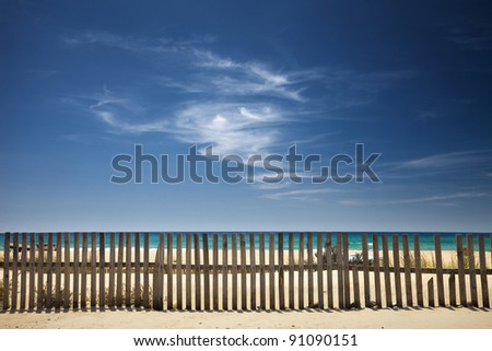 sky with clouds on the beach with a wooden fence