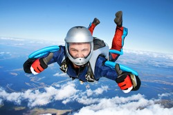 Skydiver falls through the air. All right! Thumbs up! Parachuting is fun!