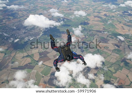 Skydiver in freefall with clouds below him