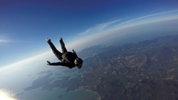 Skydiver jump over the sea and mountains