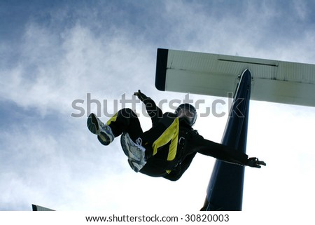 Skydiver jumps from an airplane in a sit position