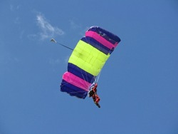 Skydiver parachutist in  red suit flying on a blue pink and yellow-green wing in the blue sky with light white soft clouds