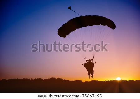 Skydiver silhouette under parachute canopy in wingsuit against sunset sky.