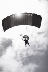 Skydiver silhouette with parachute on the background of the sun and clouds. Black and white image with color toning.
