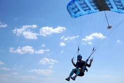 Skydiver under a blue little canopy of a parachute is flies, close-up. High-speed landing of a parachuter against the background of clouds.  USA, Michigan