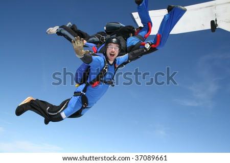 Skydiver waves at the camera