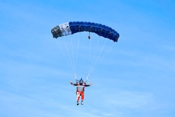 Skydiver with a blue canopy of a parachute on the background a blue sky, close-up. Skydiver under parachute is fast approaching