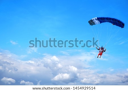 Skydiver with a blue little canopy of a parachute on the background a blue sky and white  clouds, close-up. Skydiver under parachute above the stormy clouds.  USA, Michigan Stock fotó ©