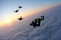Skydivers are flying above pink clouds.