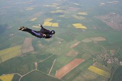 Skydivers flies past cameraman