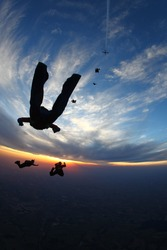 Skydivers in free fall at sunset