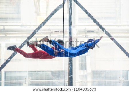 Skydivers in indoor wind tunnel, free fall simulator #1104835673