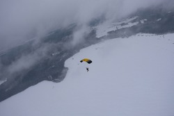 Skydiving. A parachutist with a parachute flies above a snow-covered field.