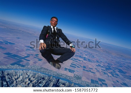 Skydiving businessman in seated position mid-air