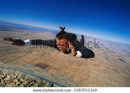 Skydiving businessman talking on mobile telephone mid-air