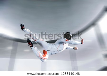 Skydiving.flying people in wind tunnel . indoor skydiving. Men in white suit