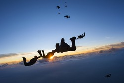 Skydiving formation at sunset