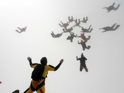 Skydiving formation inside the clouds.  The focus of the photo is on the yellow parachutist on the left.