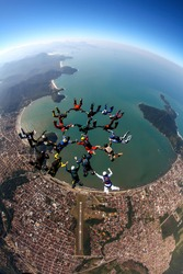 skydiving group of people in freefall over Brazilian beach