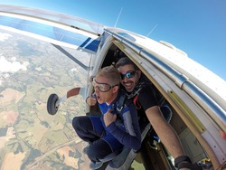 Skydiving. Happy Instructor and student screaming in aircraft door.