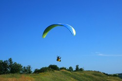 Skydiving over a green slope landscape of parachutist flying