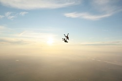 Skydiving. Sunset jump. Two guys are in the sky.