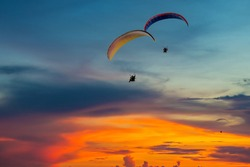 Skydiving sunset landscape of parachutist flying in soft focus. Para-motor flying silhouette with sun set. Silhouette of paraglider flying in the evening sky with sunset.