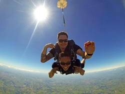 Skydiving tandem friends, against the sun photo. Fish eyes lens used.
