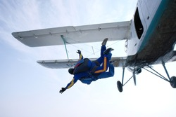 Skydiving. Tandem jump from a white biplane.