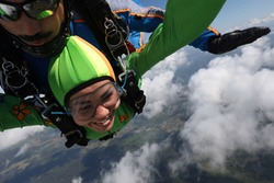 Skydiving. Tandem jump. Pretty woman and her instructor are flying in the sky.
